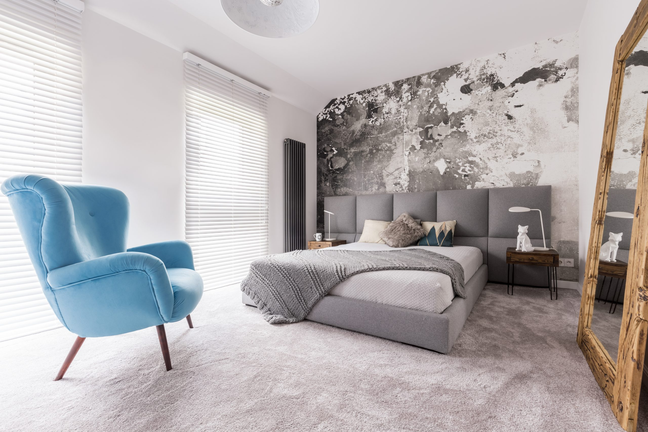 Comfortable, blue chair in a bedroom standing next to a double bed with pillows
